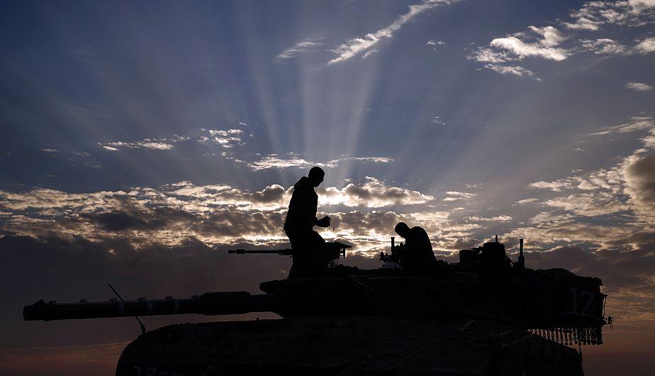 Soldados israelíes esperan ser trasladados fuera de la frontera de Gaza. (Reuters)