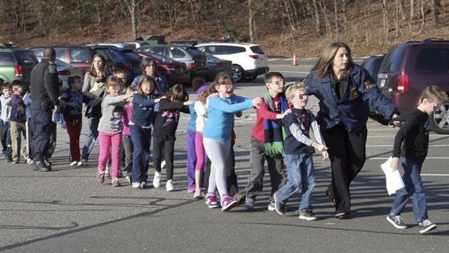 Niños evacuados por policías. (AP)