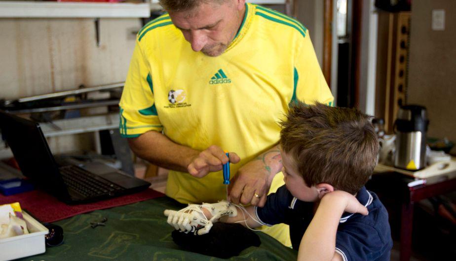 El carpintero sudafricano Richard Van As colocando prótesis al pequeño Liam. (npr.org)