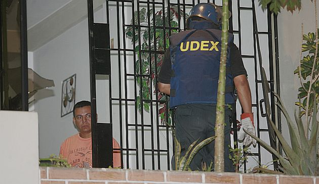 Un agente de UDEX retira una granada que extorsionadores dejaron en casa de un comerciante. (USI)