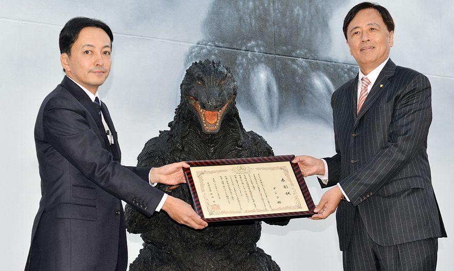 Godzilla es condecorado por el alcalde de Setagaya, a la derecha de la foto. (AFP)