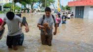 Ciudad sumergida. Las personas caminan con el agua hasta el pecho con tal de ponerse a salvo o rescatar sus pertenencias. (EFE)